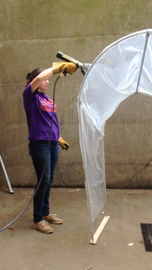 A second-year student heat-shrinks greenhouse plastic with a propane torch.