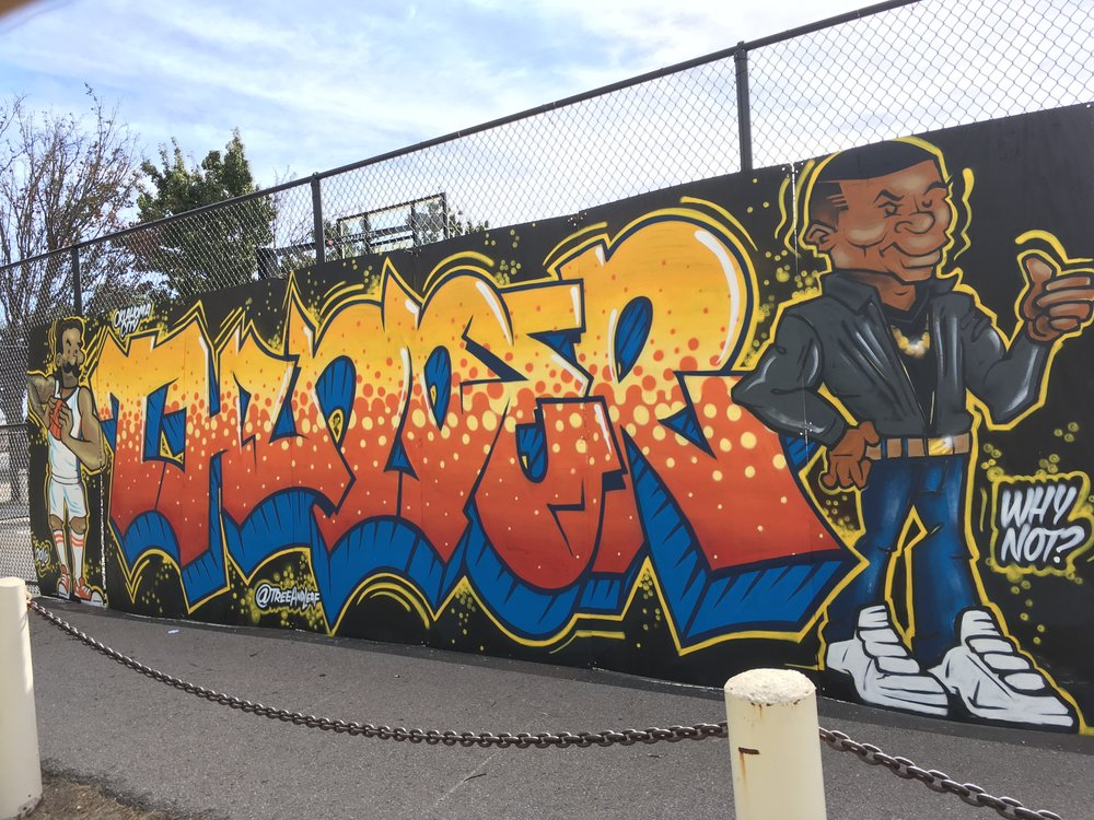 The mural is located on the corner of Hudson and Reno on the North side of the basketball courts. It is well lit at night and has a walkway right in front of it, perfect for taking some snapshots and selfies as you walk to Thunder home games!