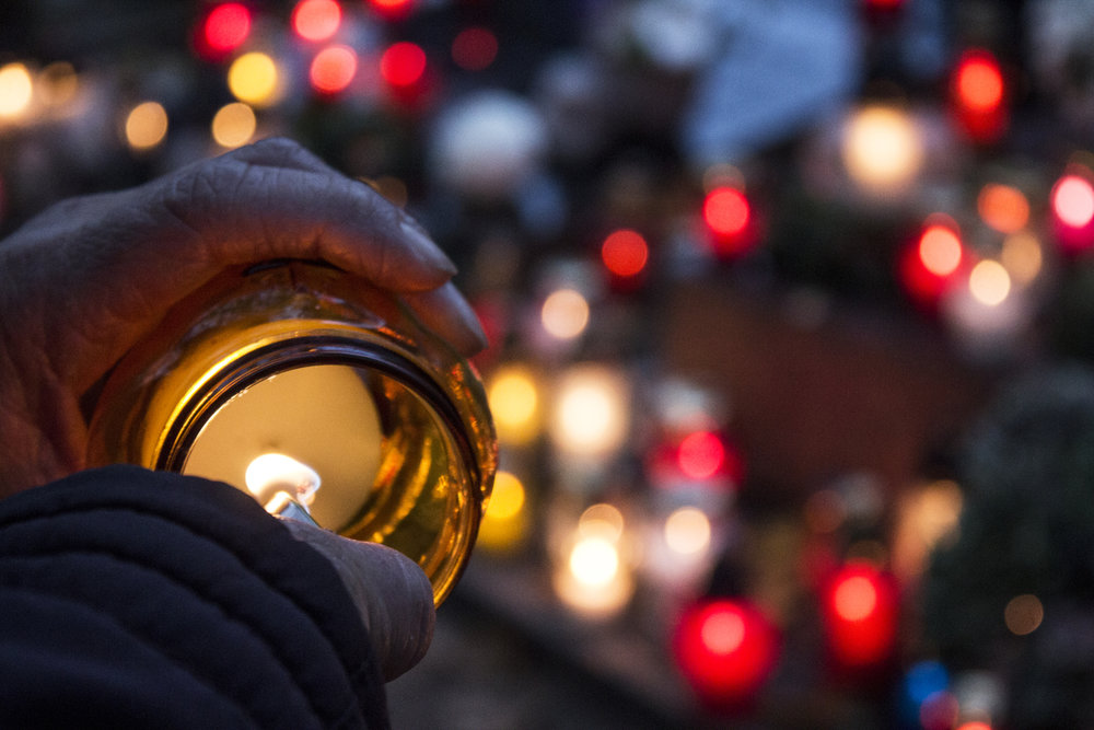 Focused nighttime image of hand lighting a candle during a vigil amongst a bokeh of candlelights. This image represents Civil Rights legislation.