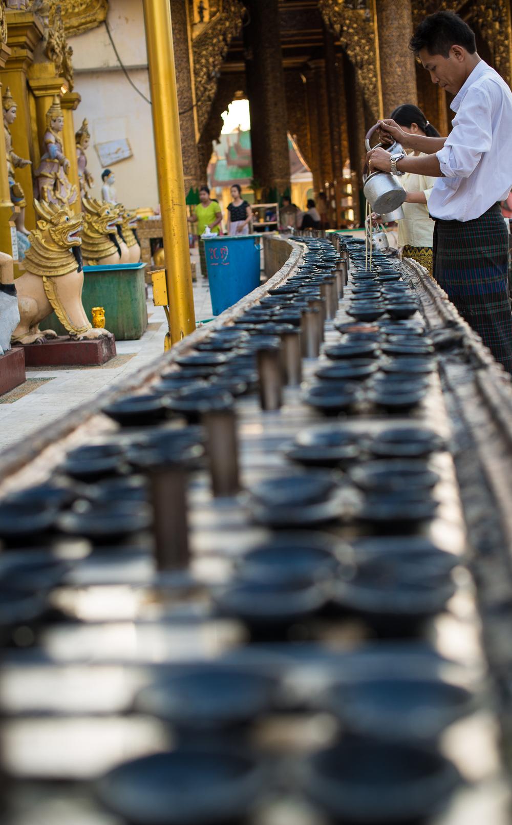 Oil lamps being filled at Shwedagon Pagoda. Yangon, Myanmar