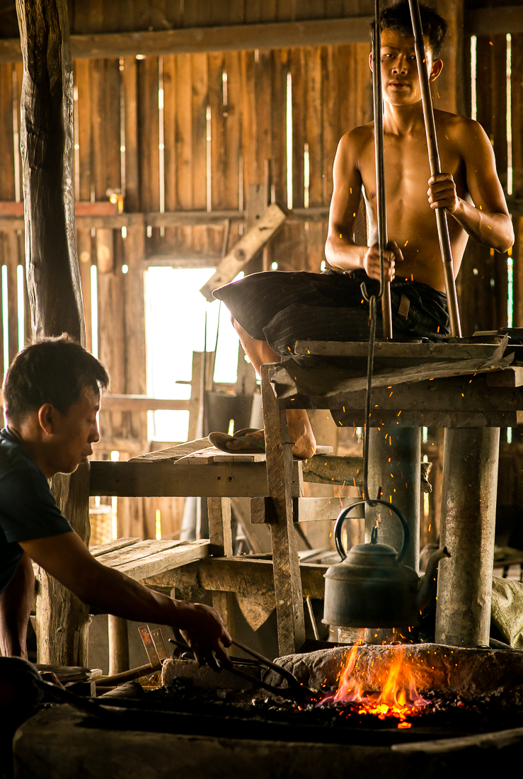 Working the bellows in a blacksmith shop. Inle Lake, Myanmar