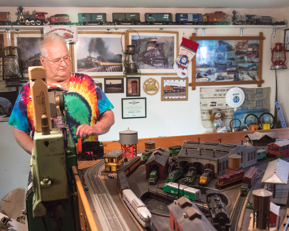 Hall operating his model train set, which fills nearly an entire room in his basement.