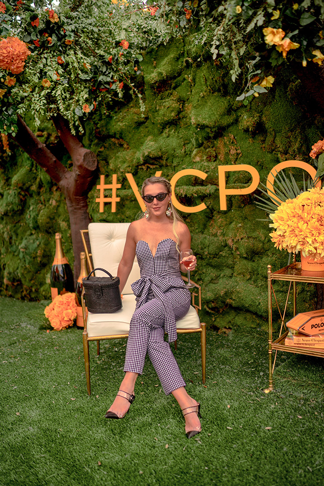 Christie Ferrari attends the Veuve Clicquot Polo Classic 2018 wearing Amanda Uprichard jumpsuit, Aquazzura heels and Ximena Kavalekas bag in New York.