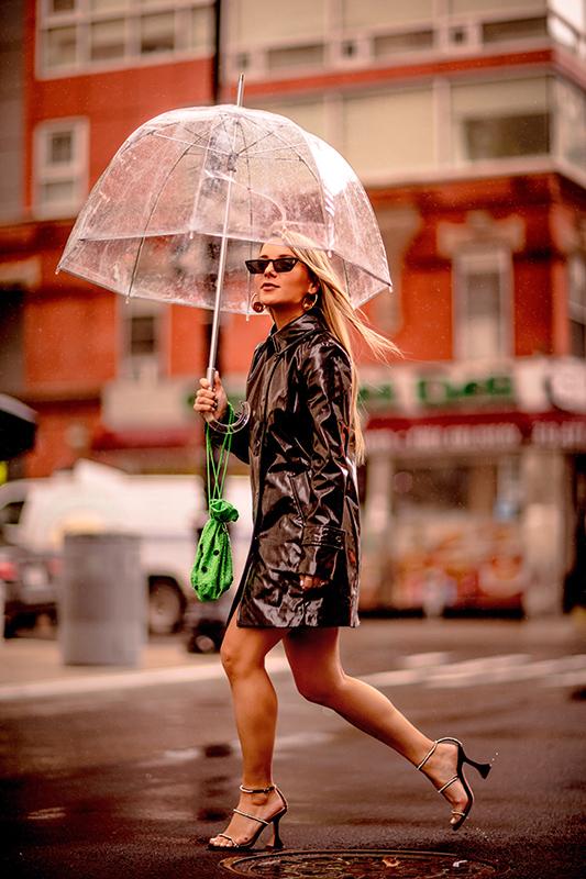 Christie Ferrari wears Banana Republic black trench coat with Ganni neon Edison Bucket Bag during NYFW outside 3.1 Phillip Lim show.