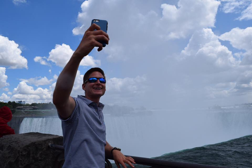 Nick taking a selfie at Niagara Falls with the youth this summer on their Choir Tour.