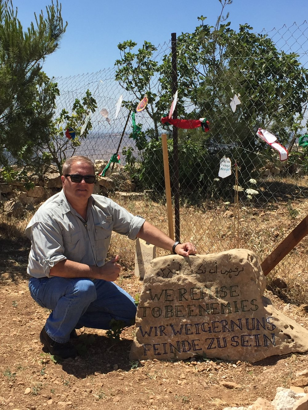 "At the entrance to the Tent of Nation. The stone says, ""We refuse to be enemies'"" in Hebrew, English, and Arabic."
