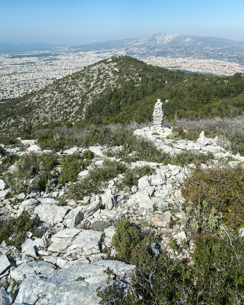 "Northern slopes of Mt. Mymettus facing north. Stone structures, or ""monuments,"" like the one in the middle ground are built by hikers and are commonly found on mountain tops or along trails in Greece."