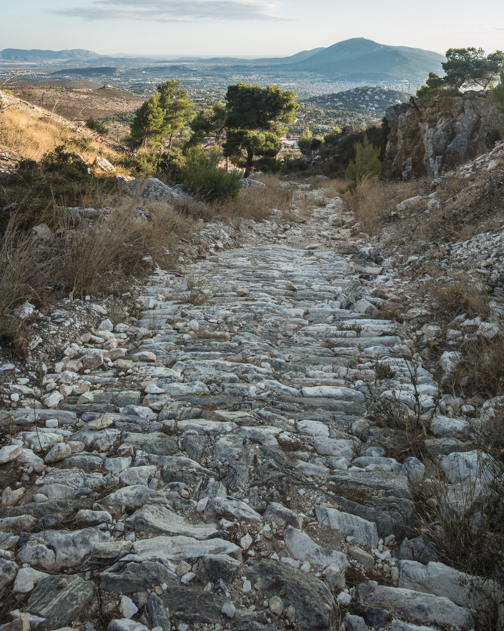 Ancient marble path leading to Athens. This path was used in ancient times to deliver marble quarried on Mt. Penteli to the center of Athens. Among other things, marble quarried here was used to build the monuments of the Acropolis of Athens, including the Parthenon in the 5th century BCE. View facing south with northern suburbs of Athens and Mt. Hymettus visible  in the background.