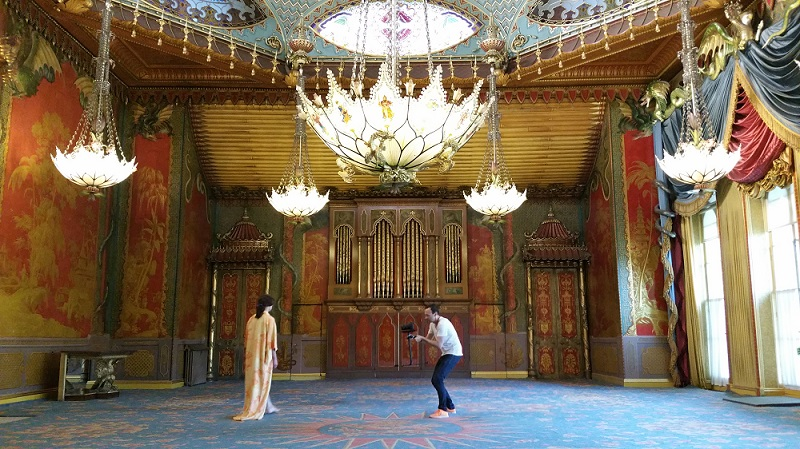 Andrew Nicholls filming the work  Gulchenrouz  with model Luca Gatti in the Royal Pavilion. Image by Alexandra Loske, with thanks to the Royal Pavilion and Museums, Brighton.