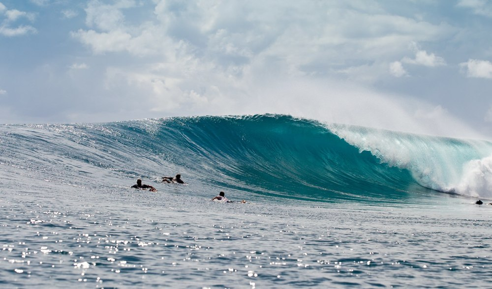 A surfer dropping into a large wave in West Sumatra during their surfing tour aboard the Ratu Motu surf charter