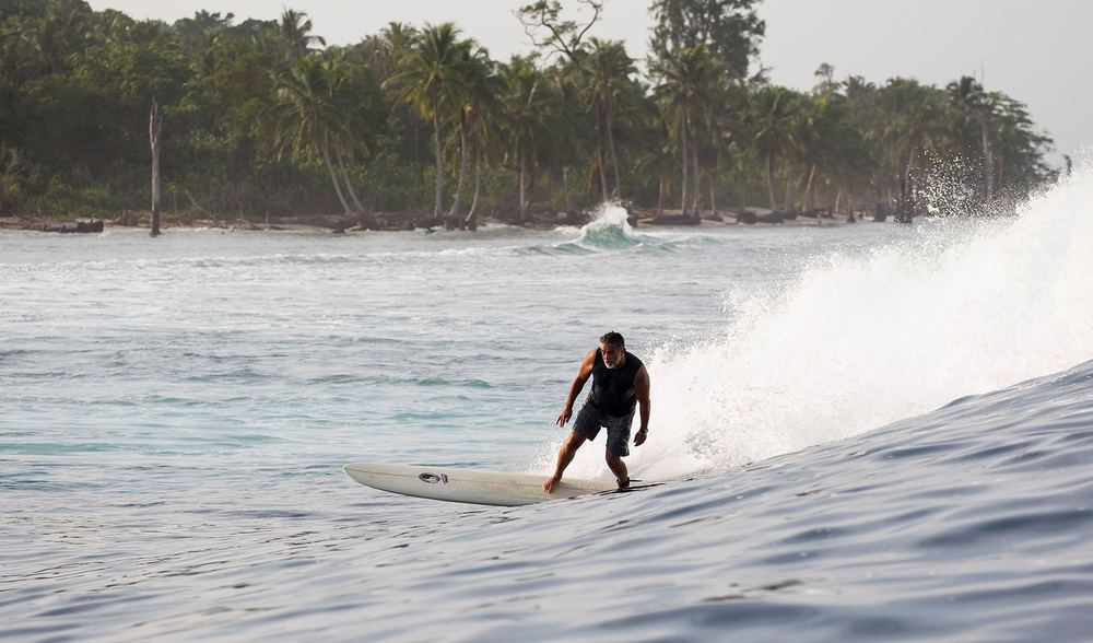 pegasus lodges and resorts, a happy surfer cruising along a wave