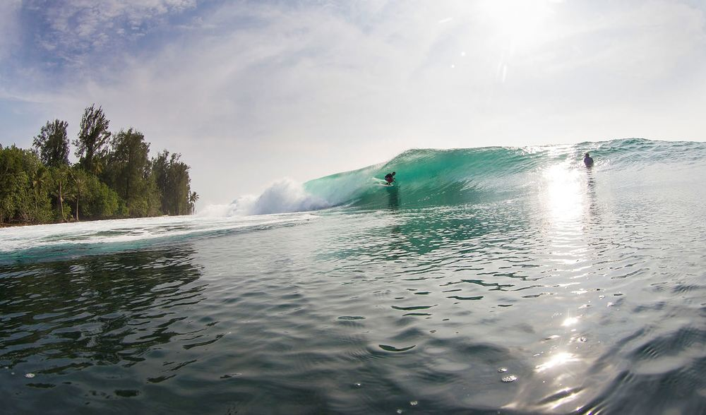 an action shot of pegasus lodges surfers enjoyin the beautiful, tropical indonesian weather