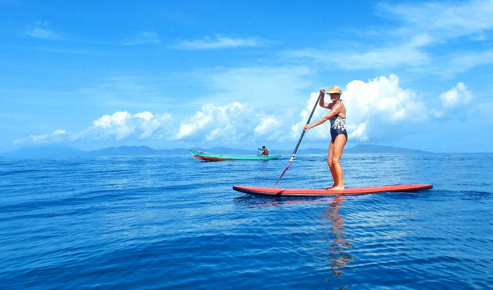 a pegasus lodges and resorts guest stand up paddleboarding around west sumatra