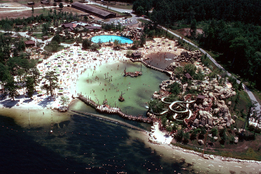Bay Cove pool with its dam separating the park from Bay Lake. Bay Cove had a sand bottom and included a tire swing, boom swing, rope climb, and T-bar drop. (Photo: ©Disney)