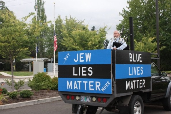 Seen here simultaneously protesting Jews and supporting police brutality, Jimmy Marr is a senior member of the Portland Daily Stormers and other Oregon Nazi groups. He is famous for his bagpipes.