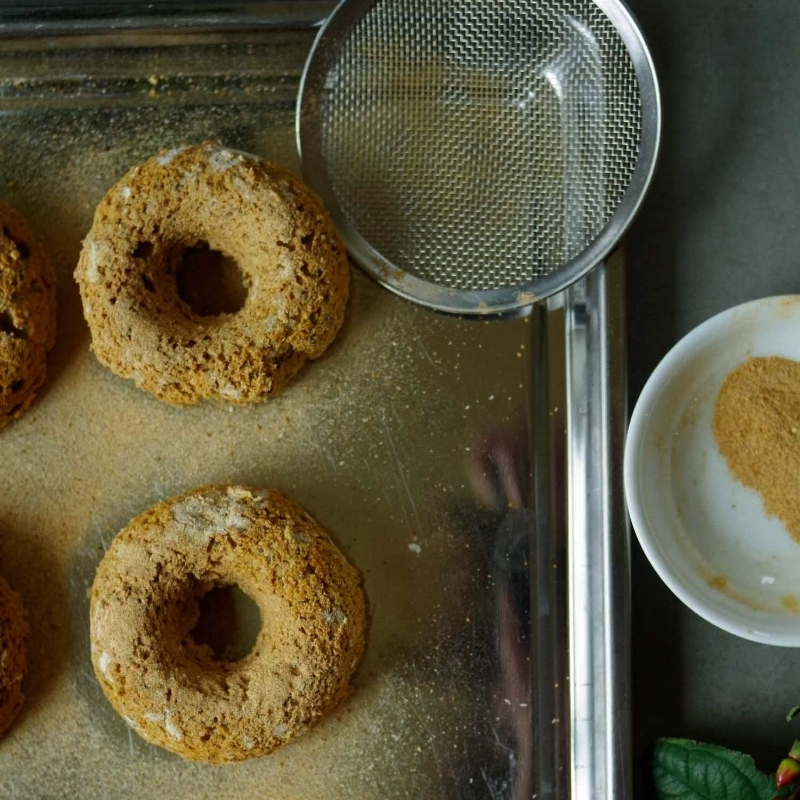Step 2:  Sprinkle the cinnamon-vanilla dust over the baked donuts.