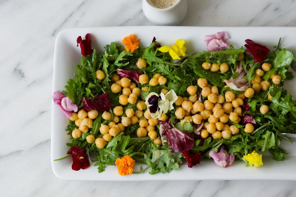For a beautiful yet easy salad, simply toss mixed greens with The Go-To Oil-Free Salad dressing, add chickpeas and garnishes, and enjoy!