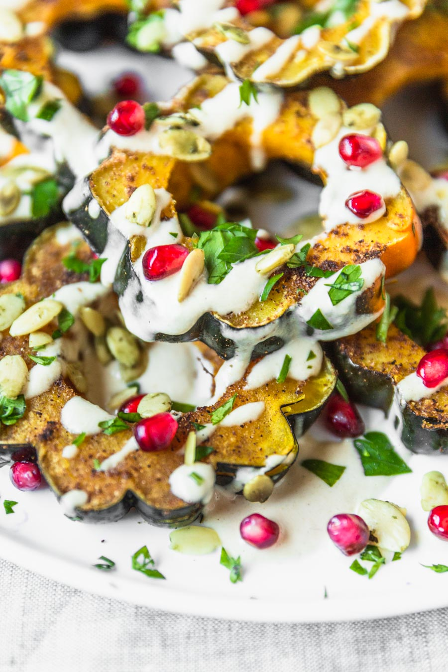 Garam Masala Roasted Acorn Squash recipe from The Ultimate Vegan Cookbook, Photo by Kari of Beautiful Ingredient. #vegan #gluten-free #thanksgiving #holiday #squash #pomegranate #tahini
