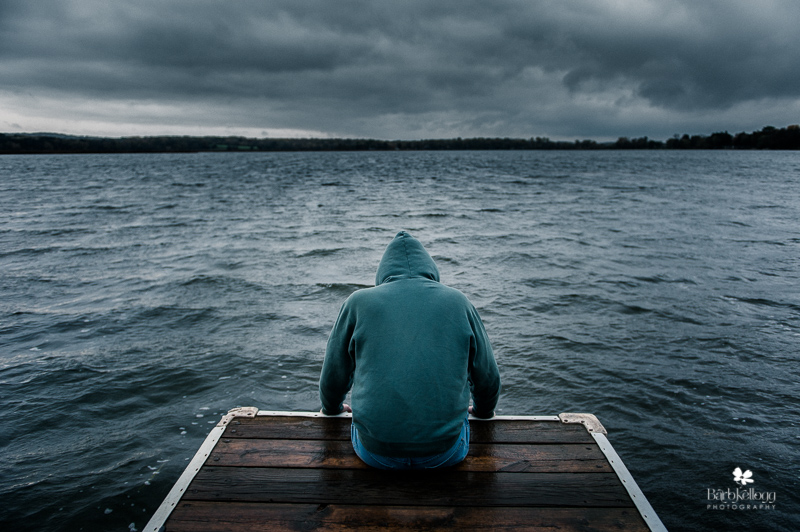 depressed person on the edge of a dock on a lake