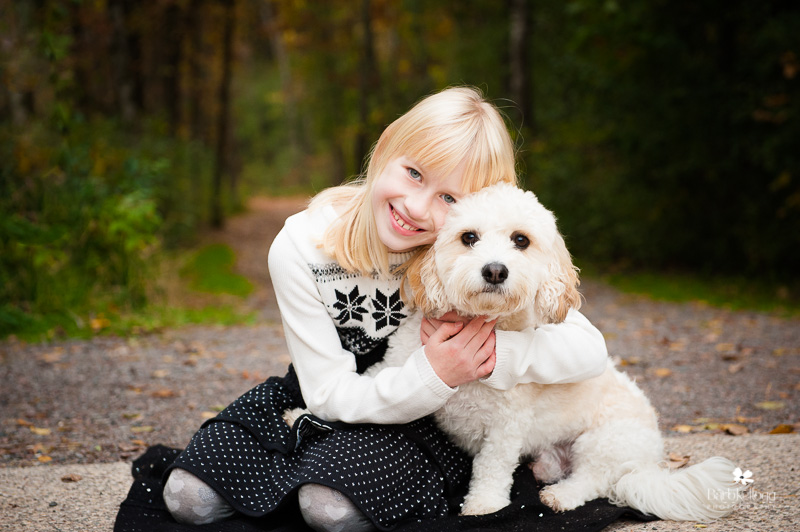 Young girl hugging her white dog