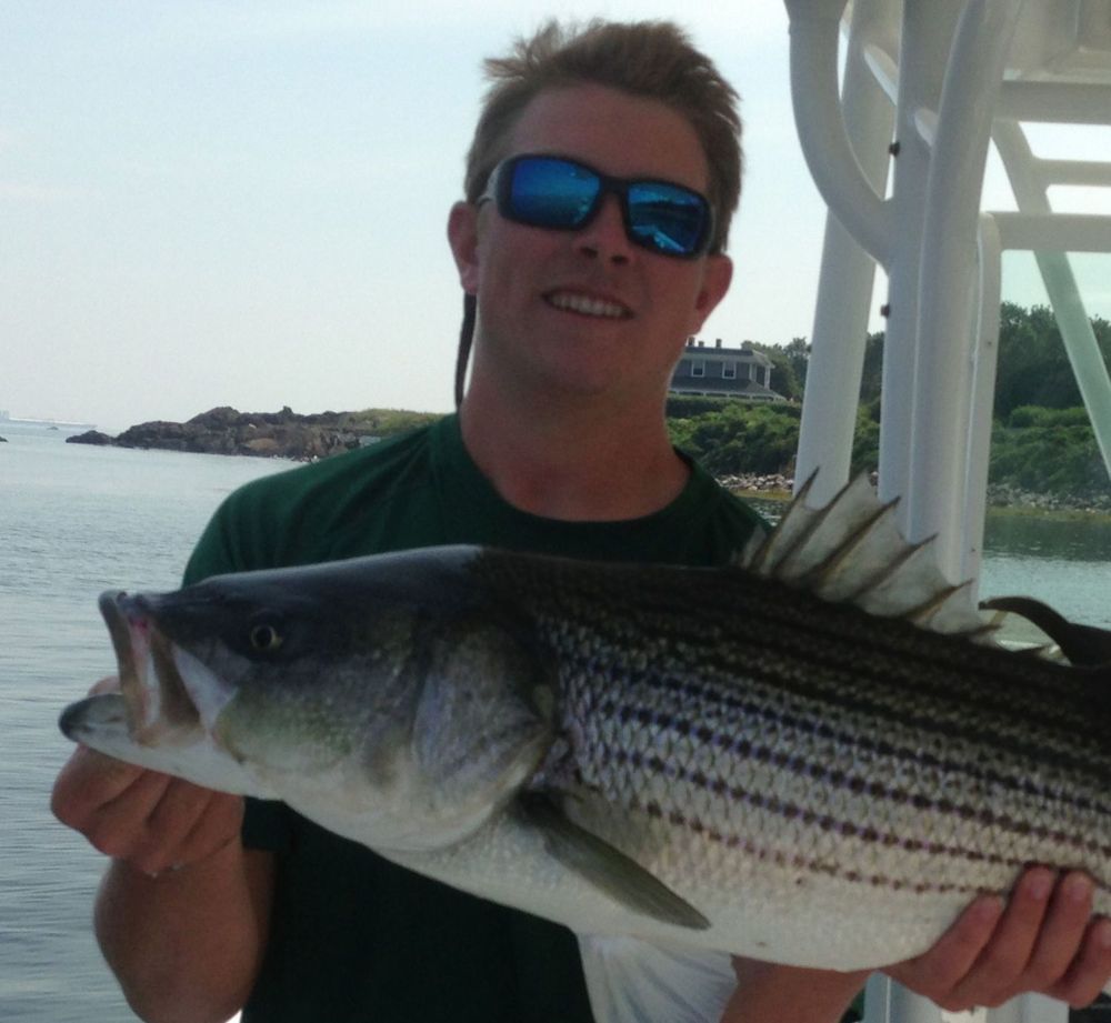 Kids Fishing Camp guide Faxon Michaud with a striped bass near Boston harbor