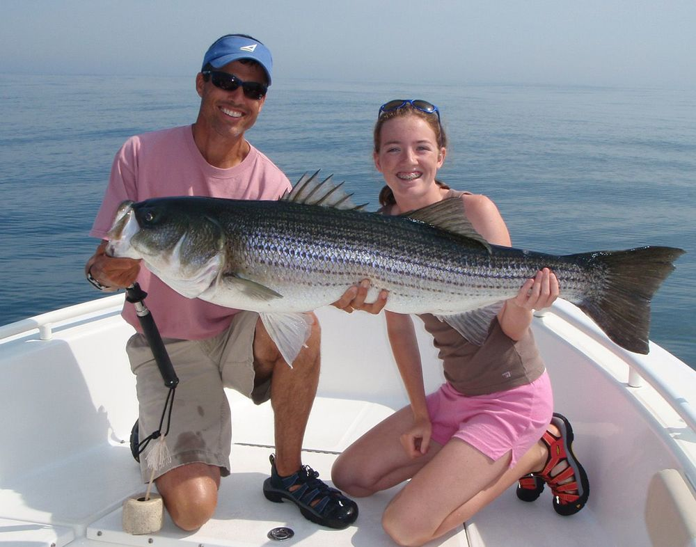 Image of Captain Randy Sigler with a large striped bass released off Marblehead