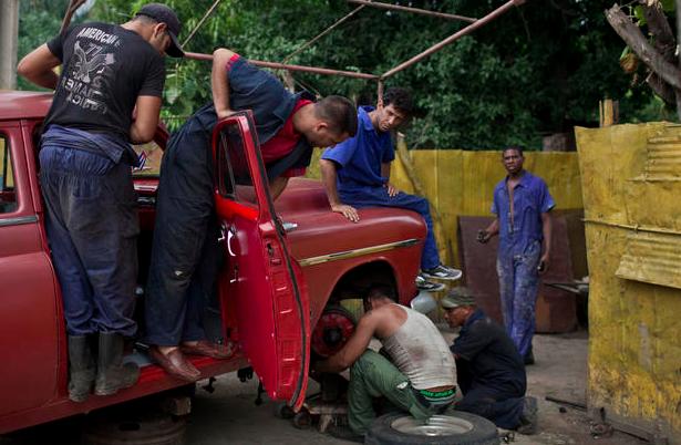 Men repair a coil spring on a classic American car in Havana, Cuba,Oct. 16, 2014.   Credit: Franklin Reyes/AP. Source:  CBS.COM