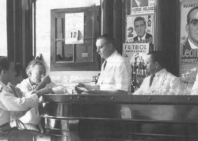 Hemingway waiting for his Papa Doble daiquiri prepared by Constante himself (standing)