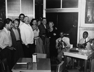 The Hemingways (1950) with friends at El Floridita with (from left to right)Gianfranco Ivancich, Roberto Herrera, unidentified man, Ernest Hemingway, unidentified woman, unidentified man, and Mary Hemingway. Two mariachi band members are sitting at table beside them.Credit Line: John F. Kennedy Presidential Library and Museum, Boston.