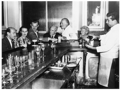 """Ernest Hemingway sitting with friends at at El Floridita (from left to right): Roberto Herrera, Byra """"Puck"""" Whittlesey, Jack """"Bumby"""" Hemingway, Spencer Tracy, Ernest Hemingway, Mary Hemingway and unidentified bartender.Credit Line: John F. Kennedy Presidential Library and Museum, Boston."""