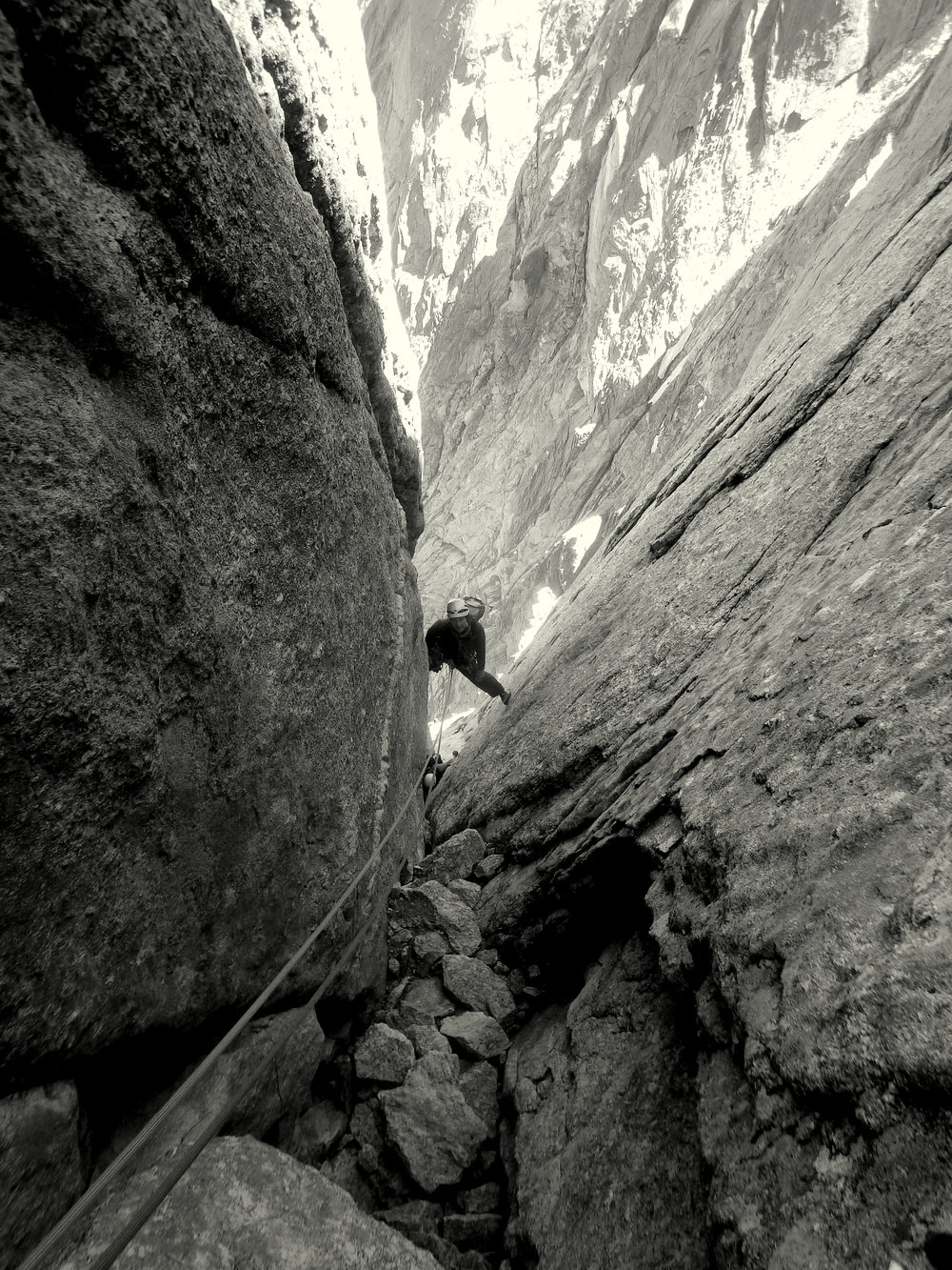 Mandy bridging her way up the exit chimneys, Cassin Route, Piz Badile