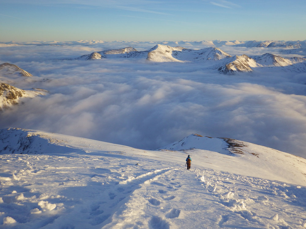 descending of the summit of ben nevis, towards the cmd arete, whilst an inversion fills the glens