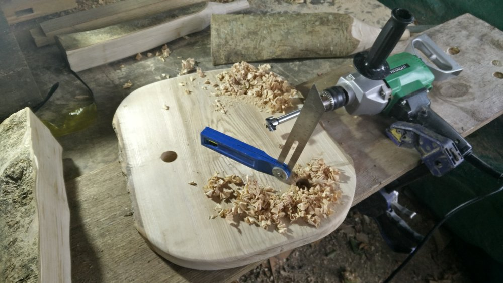 "Next use an adjustable bevel to help you to drill 1"" diameter holes at the same angle.  The picture shows the holes being drilled from the underside of the stool top, angled so that the stool legs splay outwards"
