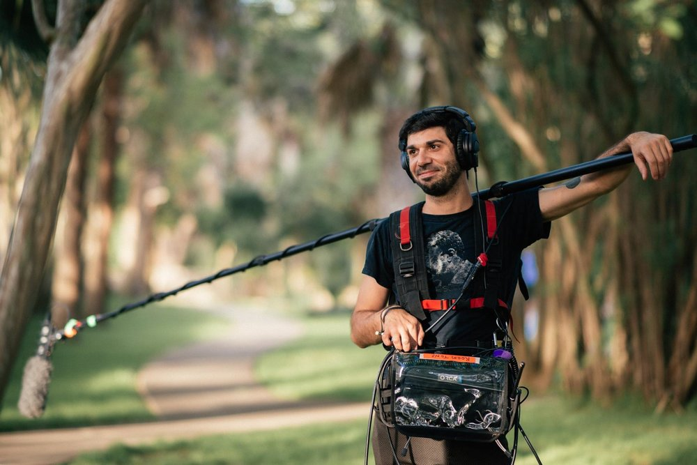 About - Tiago da Silva is a professional sound engineer, location sound mixer, boom operator, sound designer, sound editor, multi-instrumentalist, composer, orchestrator, music producer, and virtual instrument programmer. He was born in Governador Valadares, Minas Gerais, Brazil and grew up around Boston, Massachusetts before settling in Austin, Texas.Music and sound have been an ever-present part of his life from a young age. A self-taught musician, Tiago learned music on a cheap JC-Penney catalog acoustic guitar at age 10. By 16, he was performing live, composing, and recording all of his own material. By college, he'd already become a savvy studio recording engineer, where he studied music theory, and sound engineering at great depth.A graduate from Berklee College of Music, he earned a degree in Orchestrating and Producing Music for Film and Games, and is a certified ASCAP Writer and Publisher. Tiago has over fifteen years of composition and music performance experience, has produced over fifteen full length studio recordings, scored six films, and has worked both on location and in post on over thirty films in just under five years. He's passionate about the creative and collaborative process of the film industry, and driven by the power of sound to shape one's experience.