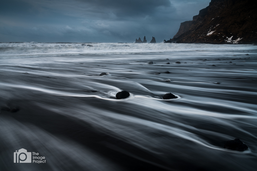 water rushes over rocks on black sand beach stormy day in vik south iceland by nathan barry the image project