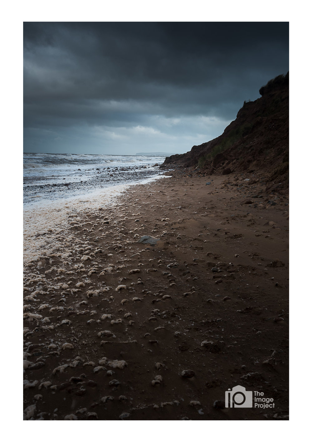 Moody skies on a frothy beach, Drigg