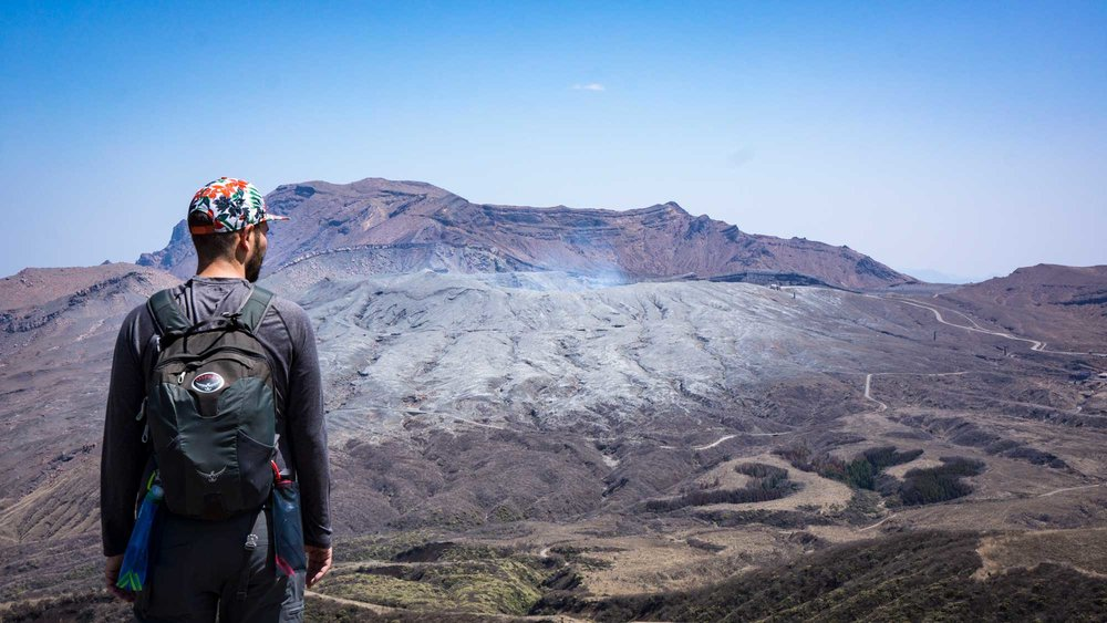 Looking at the active volcano crater after a long hike up a steep mountain