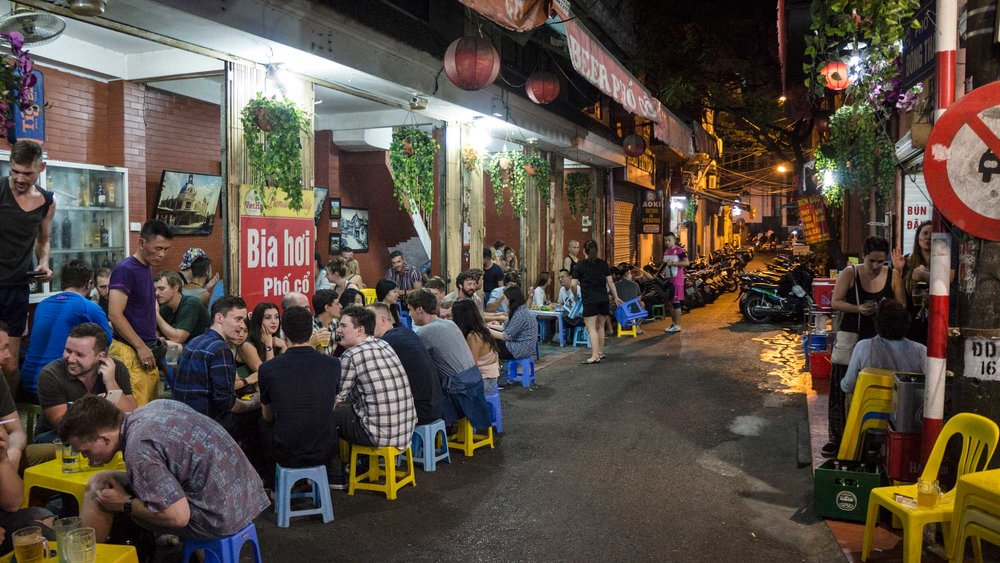Night life in Hanoi: streets are lined with endless tiny plastic chairs, tabletops, and tourists eating quick and delicious meals.