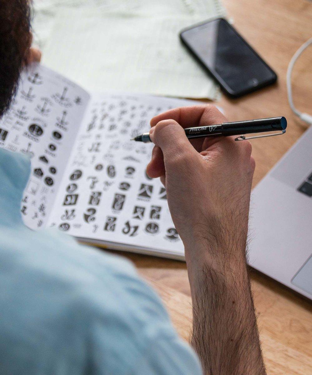 Designer drawing logos in sketchbook with a pen