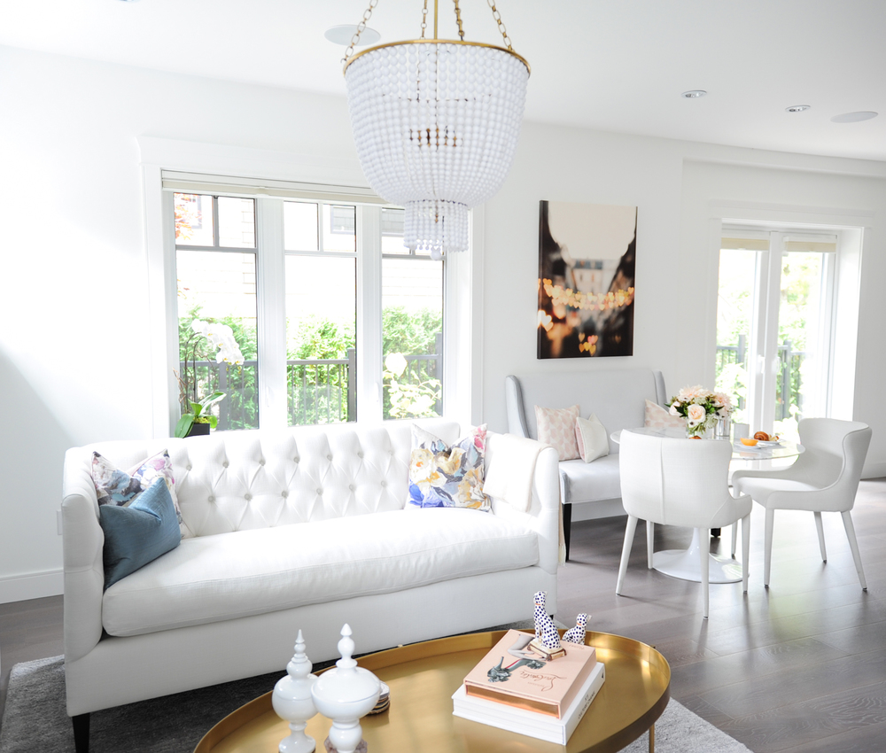 Interior Design By Chrissy Cottrell: principal designer at Curated Home By Chrissy & Co in Vancouver BC  Tufted white sofa, gold oval table and some lovely natural lighting.