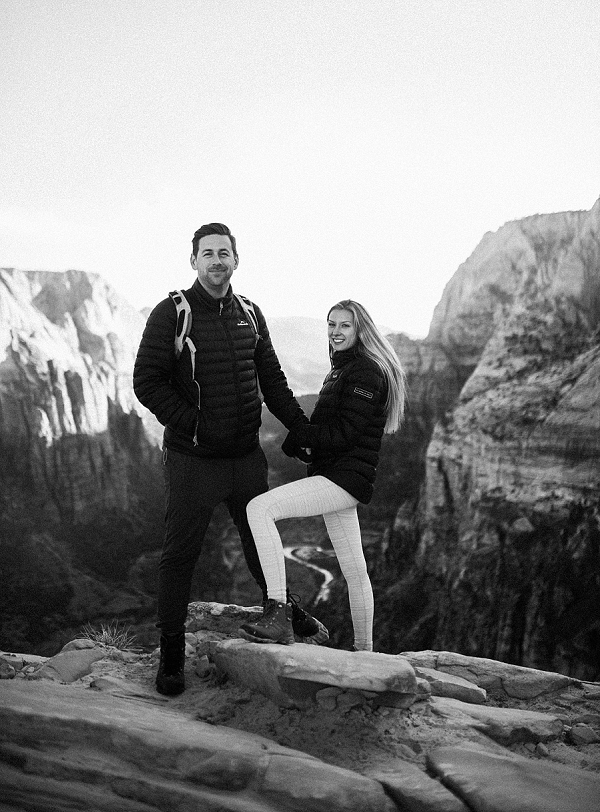 Couple together in a romantic pose at Angel's Landing in Zion National Park for their desert engagement session.