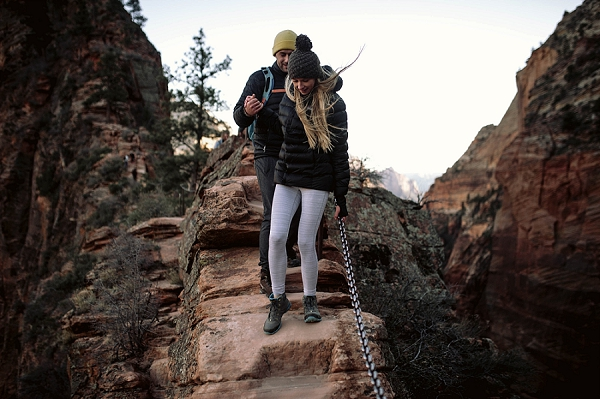 Couple hiking down Angel's Landing during their Zion National Park Engagement Shoot