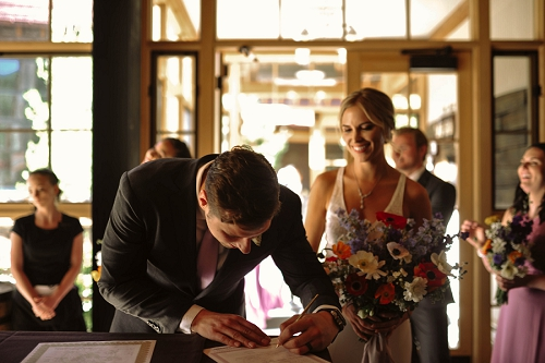 bride and groom signing their wedding certificate