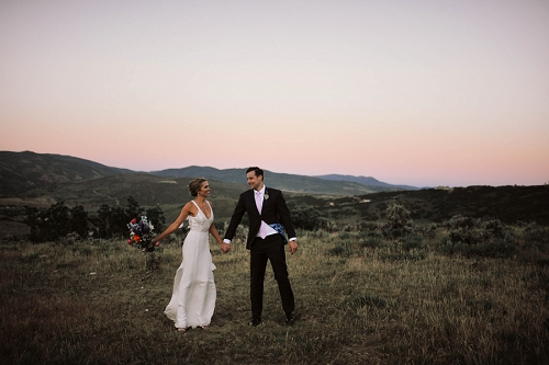 Bride and groom enjoying a windy sunset in Utah