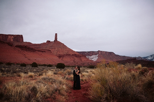 Couple stands near red rock in Southern Utah at their engagement shoot