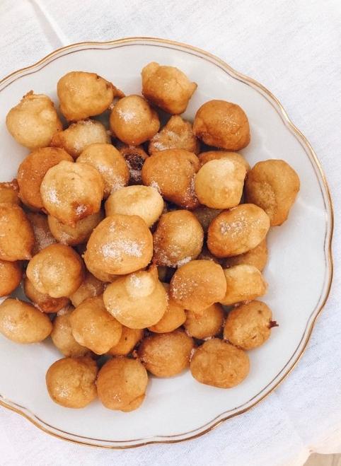 Freshly fried fritule sprinkled with sugar