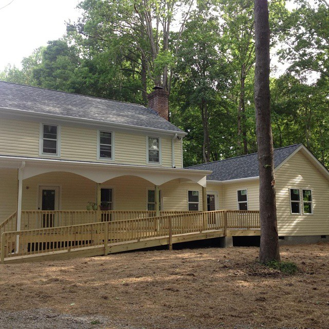 New Front elevation of existing house, with new siding and new roof and the new addition with porch and ramp.