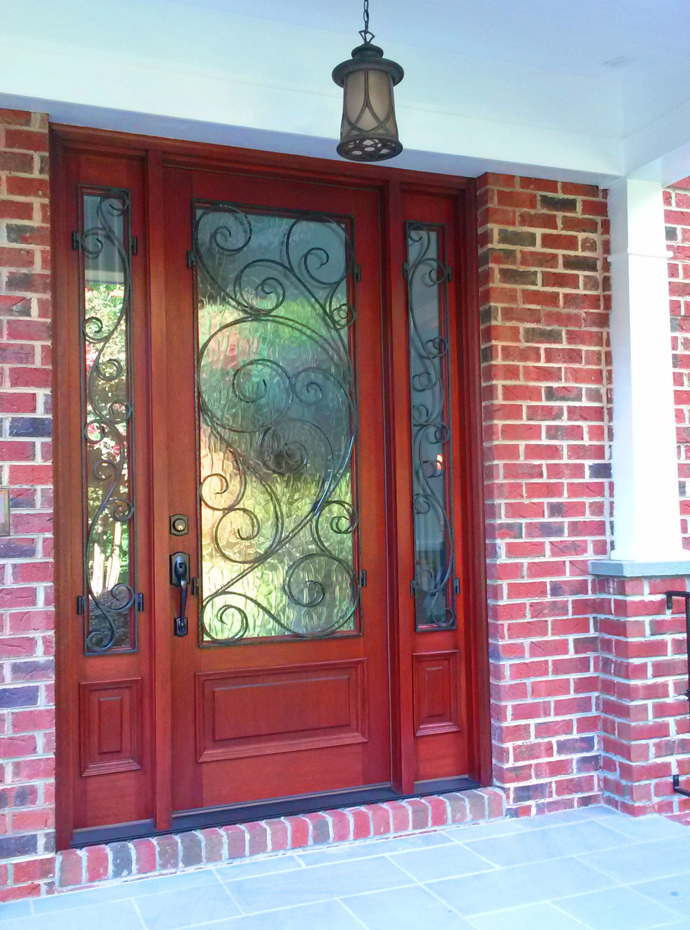 A beautiful new mahogany entry door with art glass and wrought iron detail provides a level of grandeur as one enters the porch.