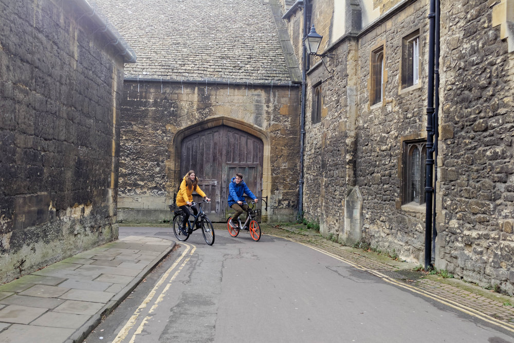 Anja and Max cycling down Queens Lane in Oxford city centre. This street is bordered by New College, Queens College and St Edmund Hall.