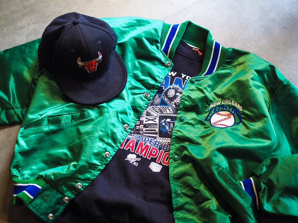 A Baseball Jacket is a must have, why not go for something super bright like this 1990s De Long New Orleans Zephyrs number. While you're piling on the sportswear you may as well top it off with a 1990s/00s pro team snapback/cap like these Chicago bulls and New York Rangers finds.
